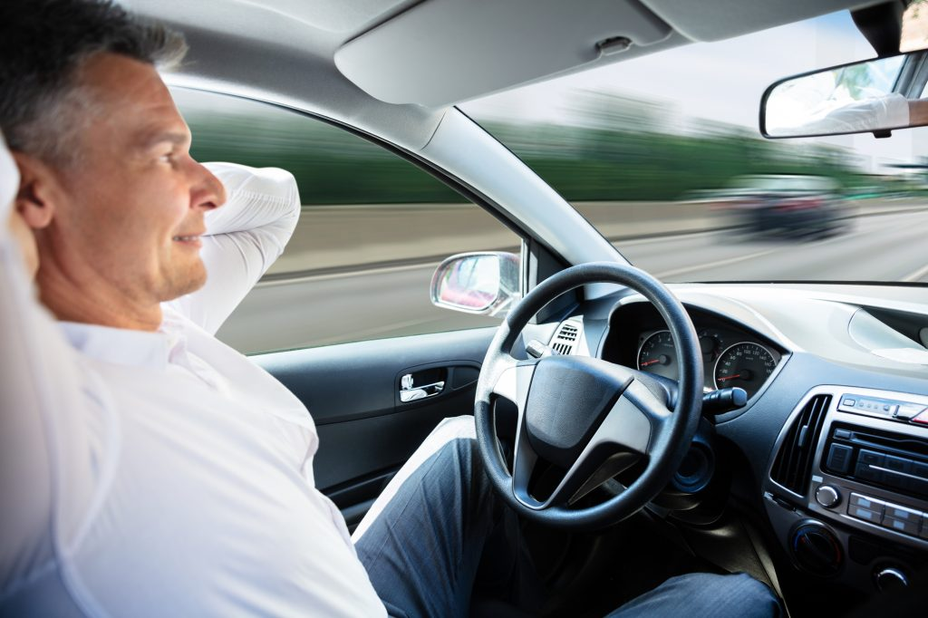 man sitting in self driving car